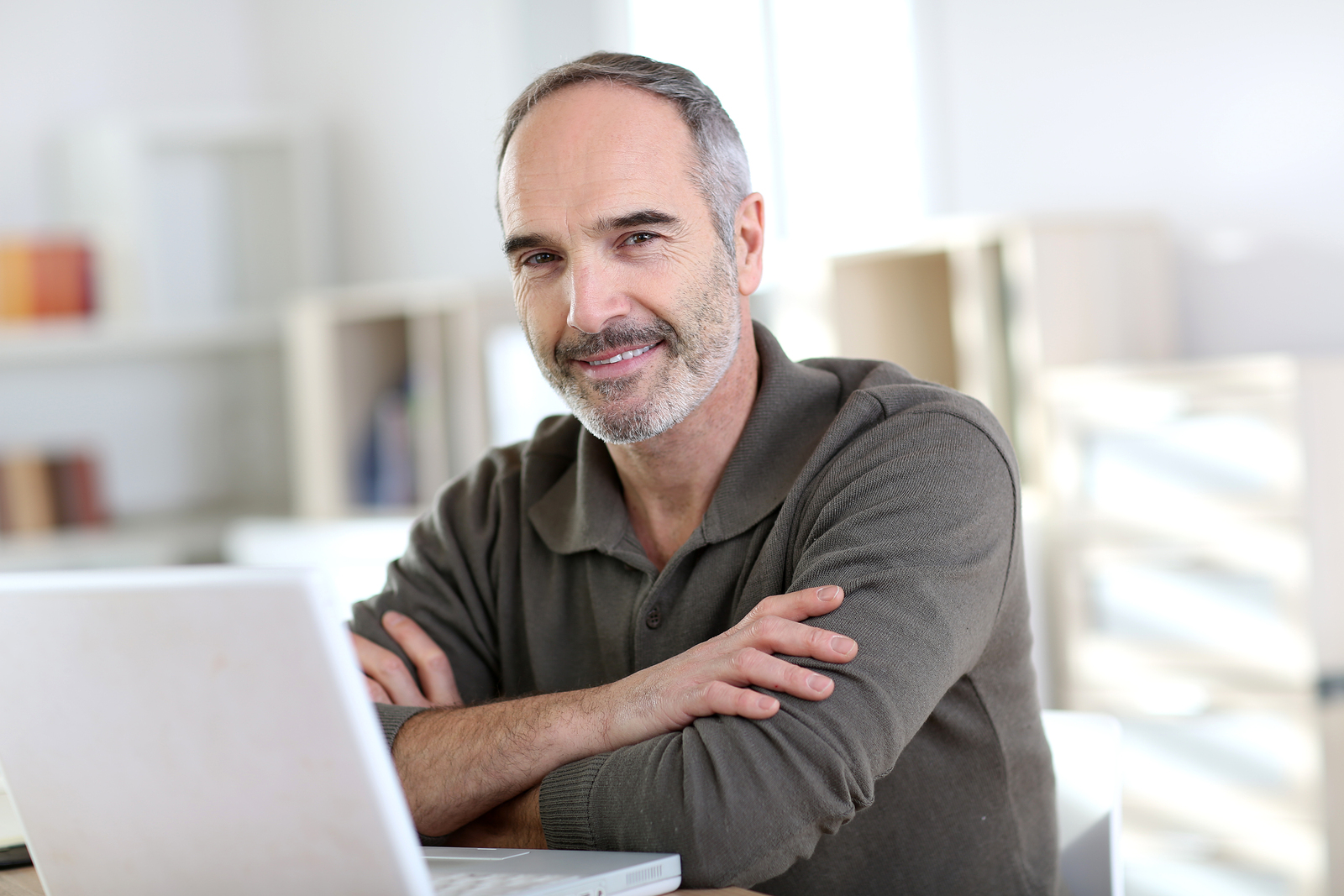Senior man working from home with laptop computer